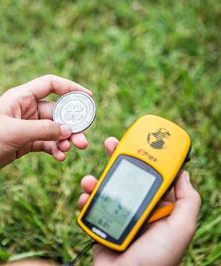 A person holding a 4-H coin and a GPS tracker