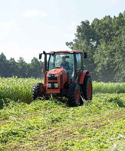 A farmer harvesting crops with a tractor